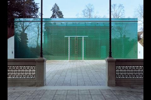 The entrance pavilion is severe in shape but highly decorative in the patterned fritting on the glass
